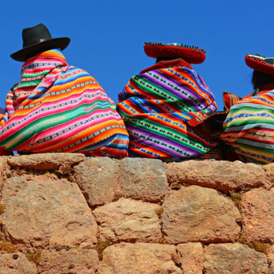 Chincheros, Peru - June 23, 2013: Quechua ladies with colorful textiles and hats sitting on an ancient Inca Wall together with a young boy with modern clothing.