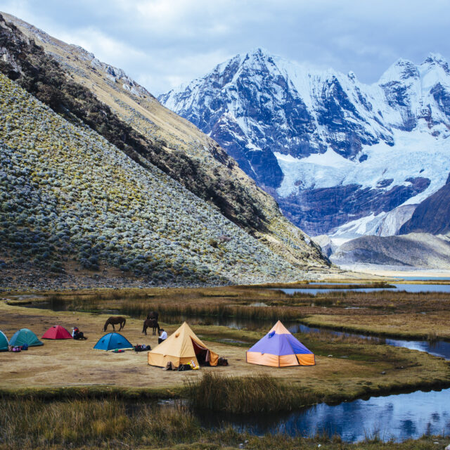 white Cordillera, Huaraz, Peru/South America - July 29, 2017: many tents on the trekking base camp at the lagoon Jahuacocha