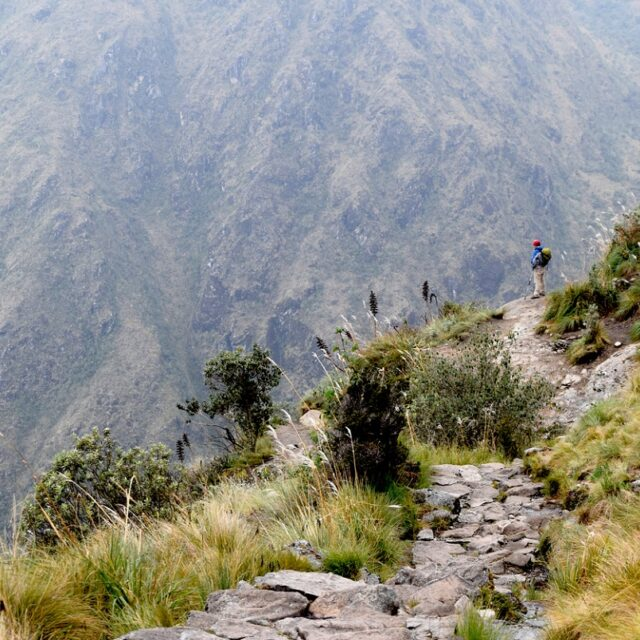 Hispanic man standing on the historical Inca trail, which goes through the mountains to Machu Picchu. Man unplugged from the busy city life, enjoying the view and peacefulness. Photo taken on the Inca trail, Peru on November 3, 2018