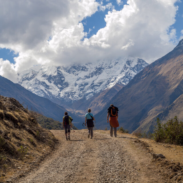 """""""Cusco, Peru - August 25, 2009: There travellers can be seen walking along a mountain road with a large mountain peak in the background partly shrouded in cloud. The road leads towards the Salcantay glacier in the Peruvian Andes near Machu Picchu and the path is a popular budget alternative to trekking the Inca trail."""""""
