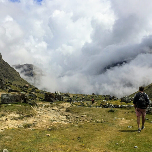 Man walking into the clouds high in the Andes Mountains along the Salkantay Trek in Peru