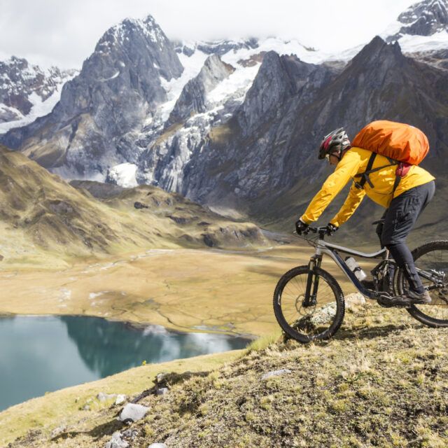 An experienced male mountainbiker is riding downhill in front of a huge rock face towards a turquoise colored lake in the Cordillera Huayhuash which is a mountain range within the Andes of Peru, in the boundaries of the regions of Ancash, Lima and Huánuco. Since 2002 it is protected within the Cordillera Huayhuash Reserved Zone. Canon EOS 700D, 1/800, f/3,5 , 18 mm.