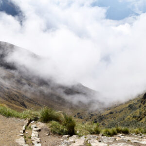 Hispanic man at the mountain pass known as Dead Woman's Pass, on the historical Inca trail, which goes through the mountains to Machu Picchu. Man at over 4000 m high altitude, seeing the clouds coming in covering the mountains. Photo taken on the Inca trail, Peru on November 3, 2018