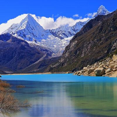 Long exposure: blurred Paron lake in Cordillera Blanca, Pirámide mountain in Andes - Ancash, Peru  Paron lake in Cordillera Blanca, Pirámide snowcapped mountain in Andes - Ancash, Peru  Laguna Parón (Parón lake) is the largest lake in the Cordillera Blanca, on the Peruvian Andes, near Huaraz, at 4185 m.